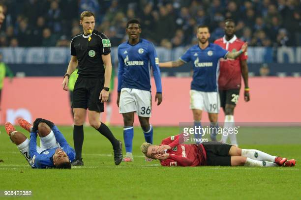 Weston McKennie of Schalke and Felix Klaus of Hannover lay injured on the ground during the Bundesliga match between FC Schalke 04 and Hannover 96 at...