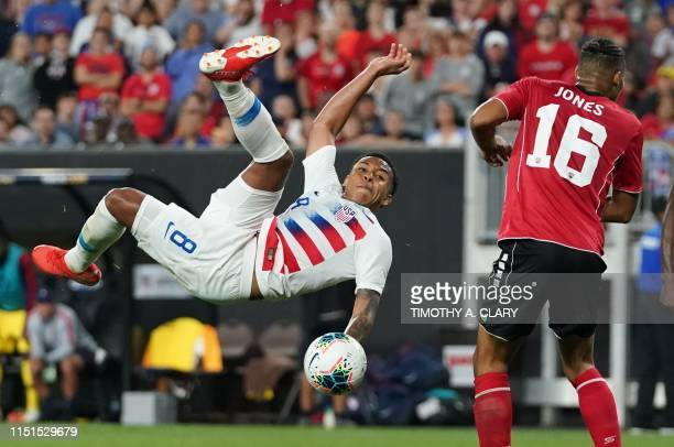 Weston McKennie of the US vies for the ball with Alvin Jones of Trinidad and Tobago during their CONCACAF Gold Cup group stage football match at...