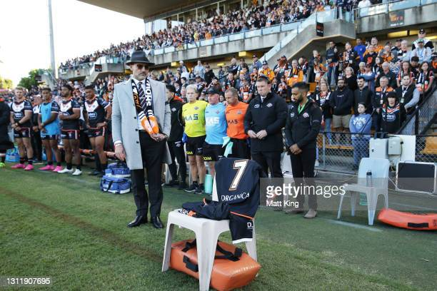 Wests Tigers Chairman Lee Hagipantelis places the number seven jersey on the first player bench seat as a tribute to the late Tommy Raudonikis during...