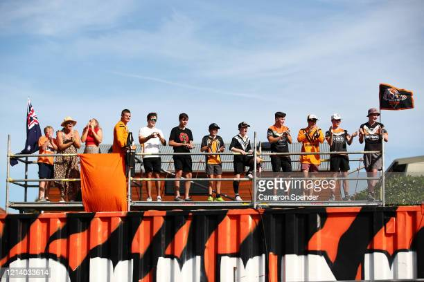 Wests Tigers fans look over their back fence on a temporary scaffolding platform to Leichhardt Oval watching the round 2 NRL match between the Wests...