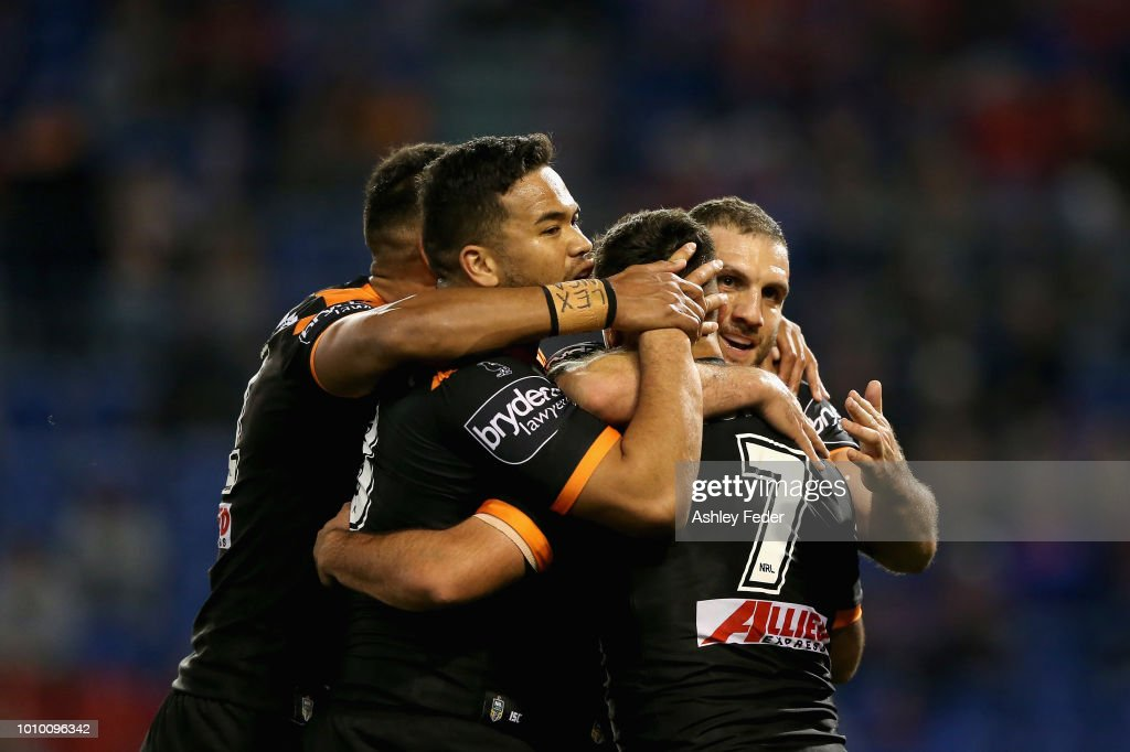 Wests Tigers players celebrate a try from Luke Brooks during the round 21 NRL match between the Newcastle Knights and the Wests Tigers at McDonald Jones Stadium on August 3, 2018 in Newcastle, Australia.