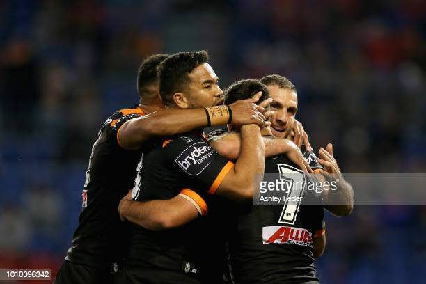 Wests Tigers players celebrate a try from Luke Brooks during the round 21 NRL match between the Newcastle Knights and the Wests Tigers at McDonald...