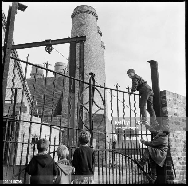 Westwood Mills, Lichfield Street, Hanley, Stoke-on-Trent, Staffordshire, 1965-1968. A group of children climbing the wrought iron gates at the canal...