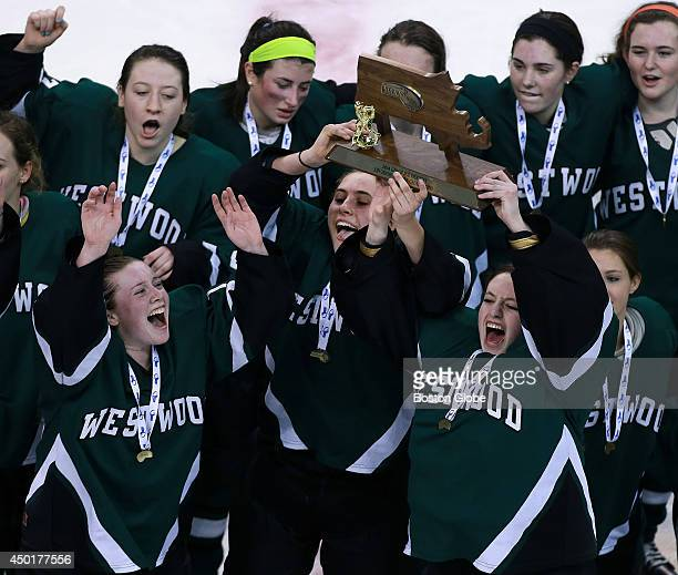 Westwood's Kelly Healey front left Kim Egizi center and goalie Siobhan Burke front right hoist the trophy as they and their teammates celebrate the...
