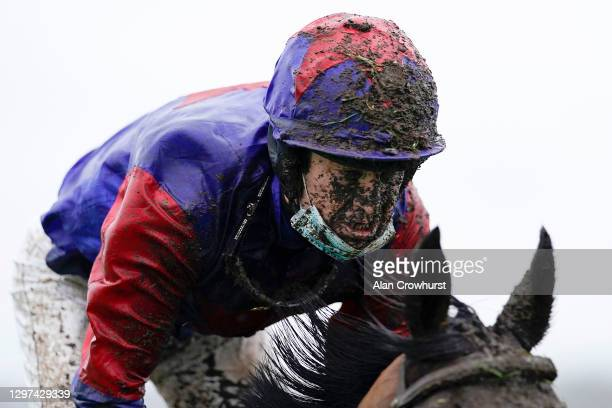 Wet and muddy Robert Dunne at Newbury Racecourse on January 20, 2021 in Newbury, England. Due to the Coronavirus pandemic, owners along with the...