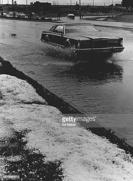 JUN 15 1982 Wet and Sloshy A driver slows down as his car goes through a small pond formed on Peoria Street just north of Interstate 70 shortly after...