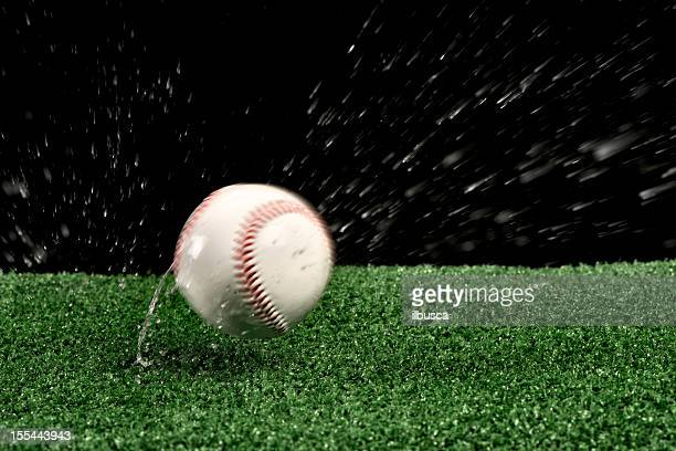 Wet baseball ball bouncing on green artificial grass