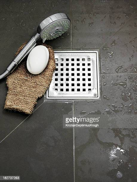 Wet bathroom with bathing utensils on the floor