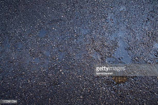 Wet black gravel road with puddles