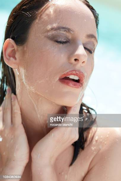 wet brunette woman with make up having a shower in sunlight - 濡れている ストックフォトと画像