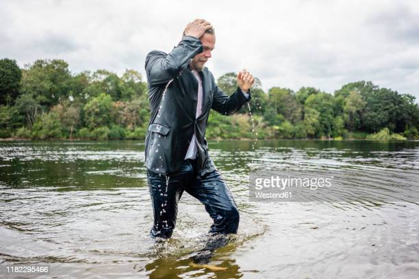 wet businessman walking in a lake - wading stock pictures, royalty-free photos & images