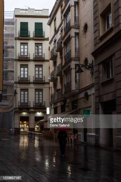 wet city street with one person with a red umbrella walking towards the camera - dorte fjalland stock pictures, royalty-free photos & images