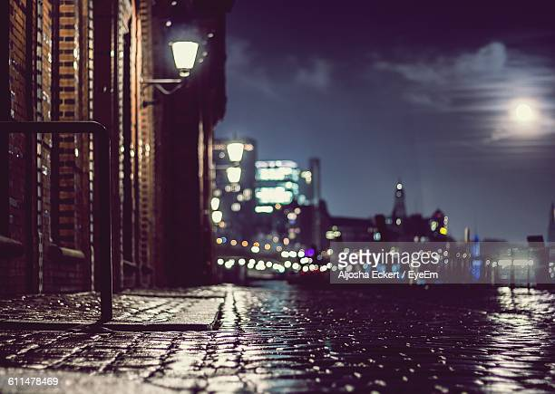 Wet Cobbled Street By Illuminated Building At Night