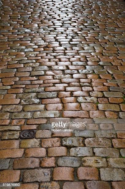 wet cobblestone street in le puy - ルピュイ ストックフォトと画像