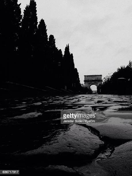 Wet Cobblestone Street Leading Towards Arch Of Titus Against Sky