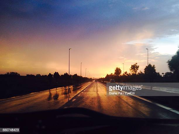 Wet Country Road Seen Through Car Windshield Against Sky During Sunset