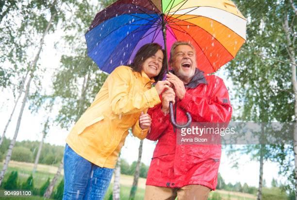 Wet couple hiding under colorful umbrella. Debica, Poland
