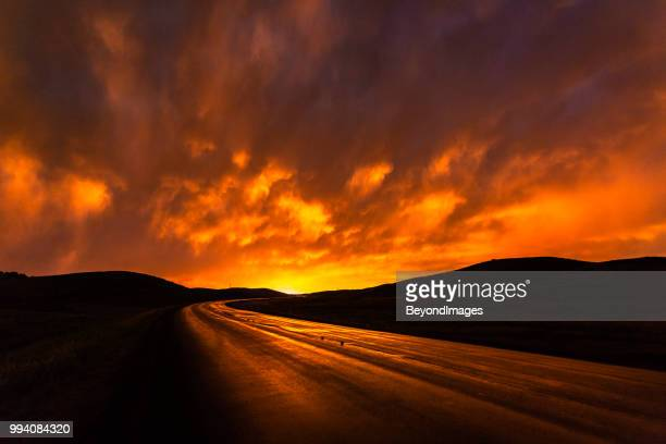 wet fiery red highway reflecting storm clouds at sunset in south dakota - extreme weather stock photos and pictures