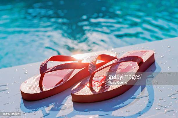 wet flip flops poolside with the sun shining on the water - ciabatta infradito foto e immagini stock