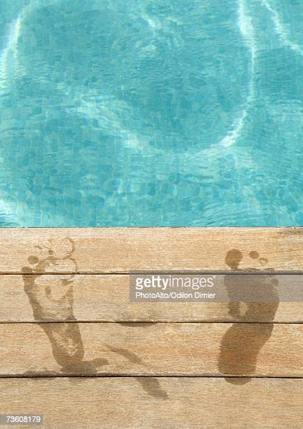 wet footprints by edge of swimming pool - poolside stock pictures, royalty-free photos & images