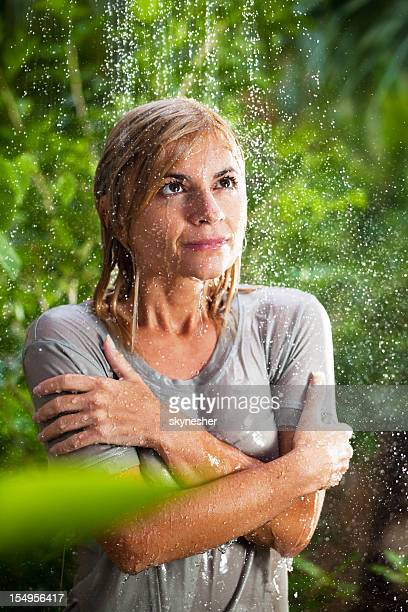Wet girl during tropical rain in the jungle.