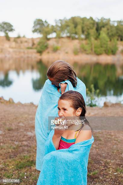wet girl wrapped in towel eating hot dog while standing with sister at lakeshore - snag tree stock pictures, royalty-free photos & images