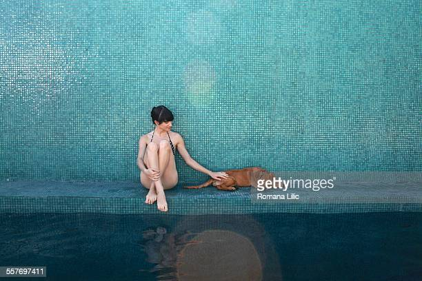 Wet golden retriever puppy sitting with woman in a bikini her owner at the edge of a blue tiled pool