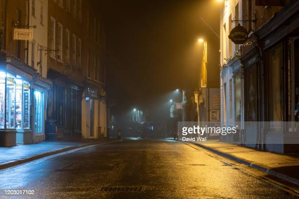 a wet high street with historic buildings with street lights glowing on a misty winters night. upton upon severn, uk - stadsstraat stockfoto's en -beelden