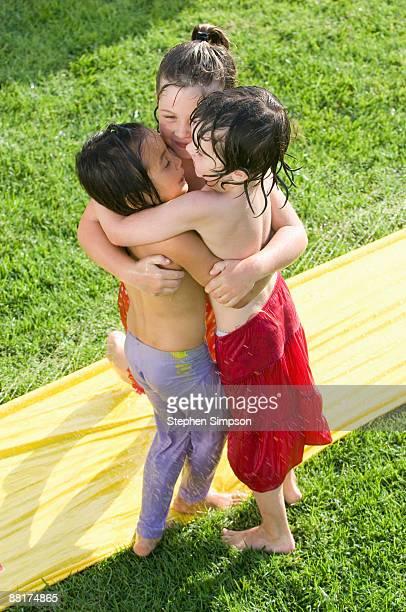 Wet kids hugging on water slide