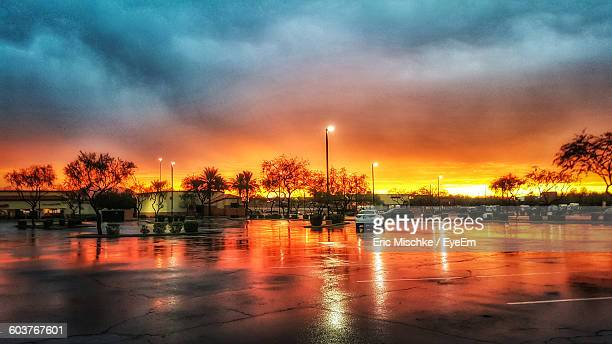Wet Parking Lot Against Cloudy Sky During Sunset