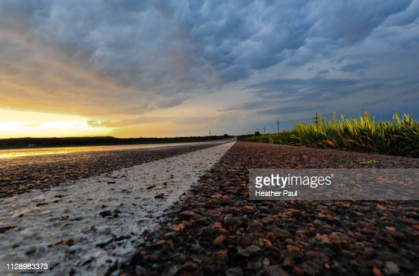 wet road and gloomy clouds at dusk after storm - heather storm stock photos and pictures
