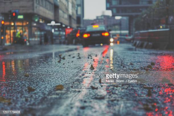 wet road in city during rainy season - extreme weather stock pictures, royalty-free photos & images