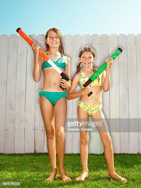 2 wet sisters pose with water toys