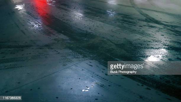 wet skid marks of vehicle tires on asphalt with light reflections - bagnato foto e immagini stock