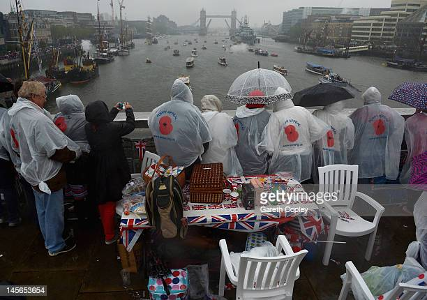 Wet spectators watch from London Bridge as the flotilla of 1000 boats sails down the River Thames towards Tower Bridge during the Diamond Jubilee...