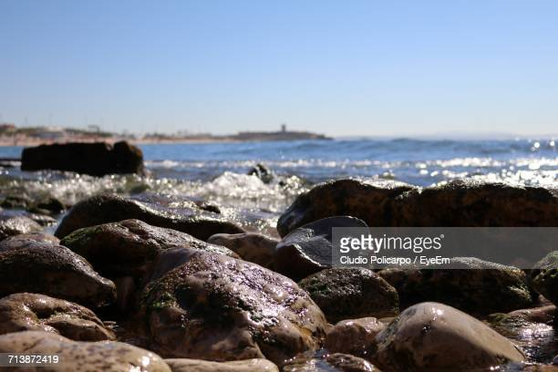 Wet Stones At Beach Against Blue Sky