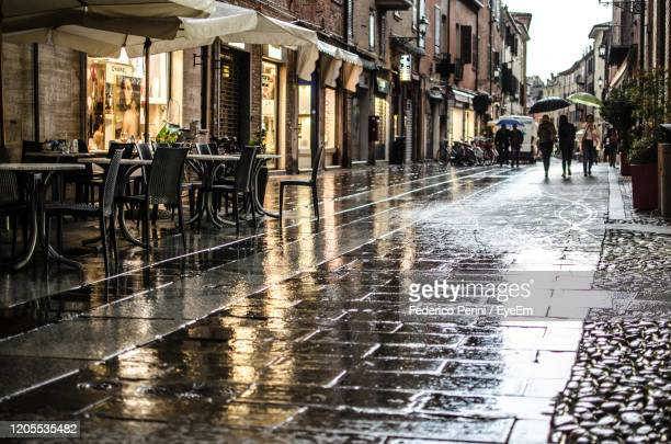 wet street amidst buildings in city during rainy season - ferrara stock pictures, royalty-free photos & images