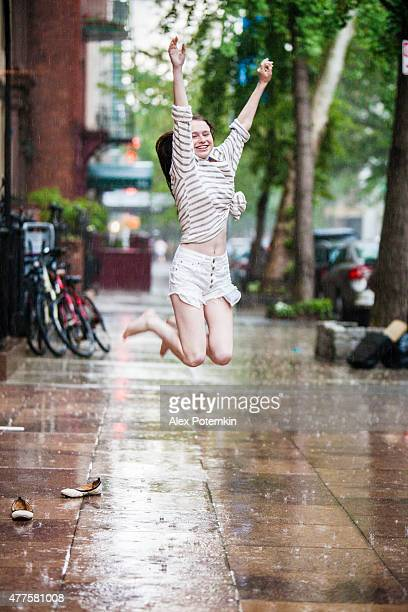 Wet teenager girl dancing and jumping under the summer rain