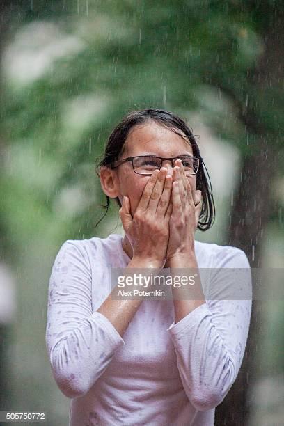Wet teenager girl have fun under the summer rain