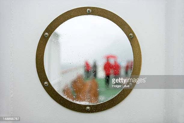 Wet view through porthole to deck on cruiseship MS Deutschland (Reederei Deilmann), Beagle Channel.