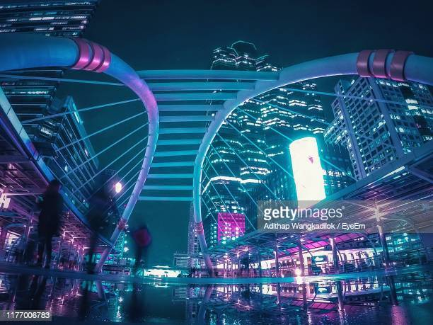 wet walkway amidst modern illuminated buildings in city - elevated walkway stock pictures, royalty-free photos & images