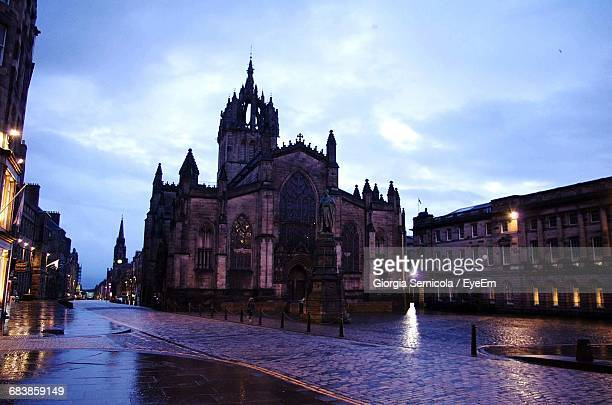 Wet Walkway Leading Towards St Giles Cathedral Against Sky At Dusk