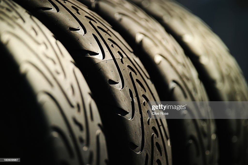 Wet weather tyres sit in the paddock during previews for the