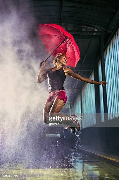 Wet woman jumping with umbrella