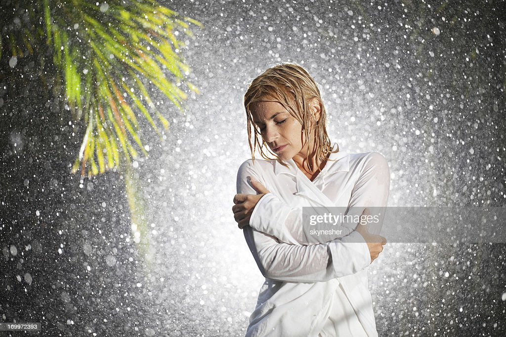 Woman standing in overcoat holding umbrella singing in the