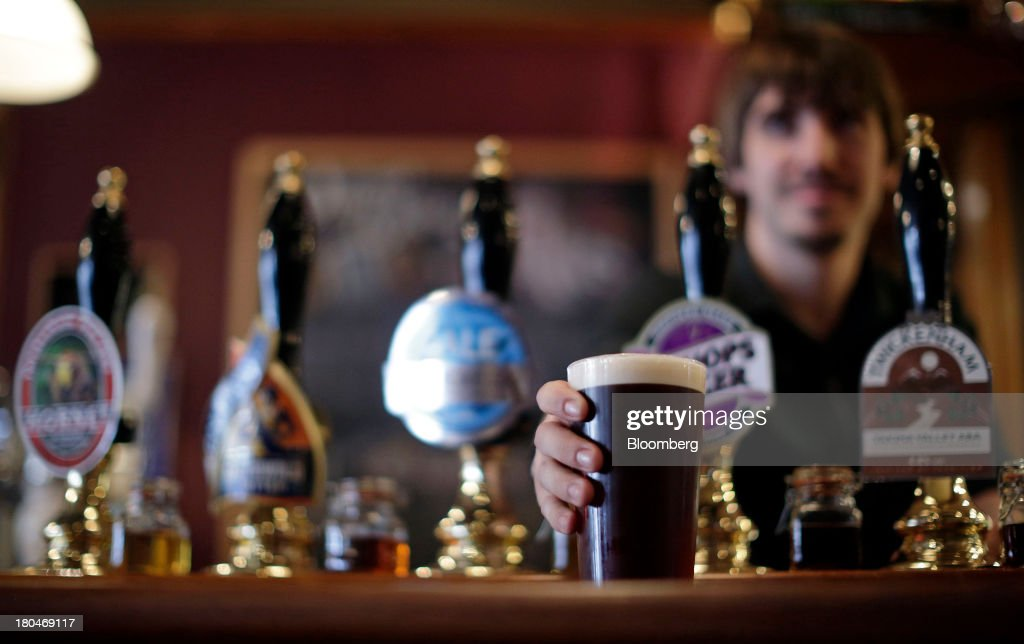 Wetherspoon Plc employee holds a pint of bitter beer in this arranged photograph at one of the company's pubs in London, U.K., on Friday, Sept. 13, 2013. JD Wetherspoon, who reported full year sales today, are planning to move into the Irish market next year, Chairman Tim Martin said in a recent interview. Photographer: Matthew Lloyd/Bloomberg via Getty Images