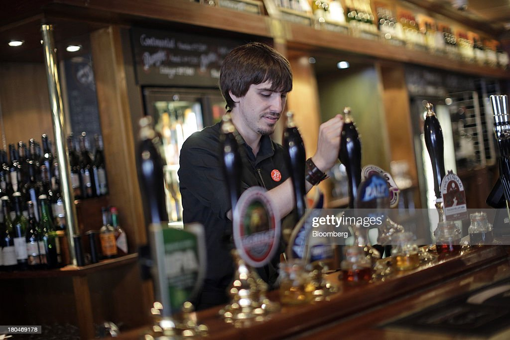 Wetherspoon Plc employee pulls a pint of Bishop's Finger bitter as he works behind the bar at one of the company's pubs in London, U.K., on Friday, Sept. 13, 2013. JD Wetherspoon, who reported full year sales today, are planning to move into the Irish market next year, Chairman Tim Martin said in a recent interview. Photographer: Matthew Lloyd/Bloomberg via Getty Images