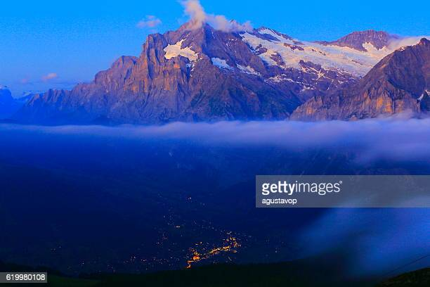 Wetterhorn above illuminated Grindelwald at evening, Swiss Alps