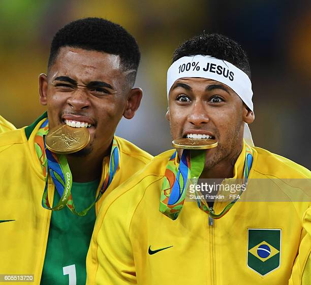 Weverton and Neymar of Brazil bite their medasl after the Olympic Men's Final Football match between Brazil and Germany at Maracana Stadium on August...