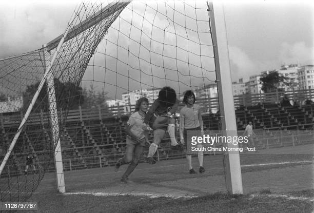 What a close shave A Kowloon Motor Bus soccer team player kicking away a loose ball in front of his goalmouth while Eastern striker Geoff Gravett and...